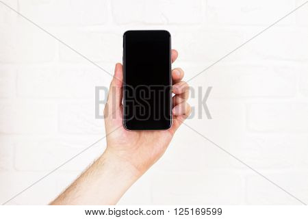 Male hand holding blank black smartphone on white brick background. Mock up