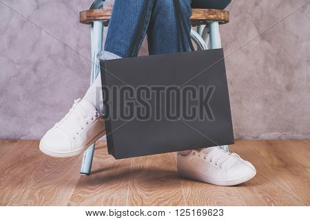Closeup of crossed legs on chair with blank shopping bag. Mock up