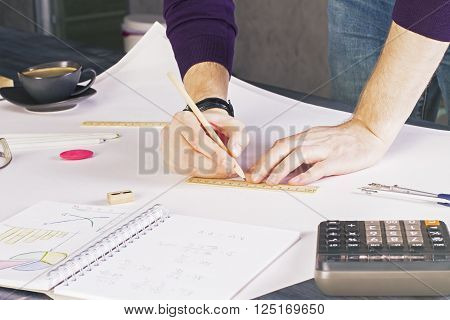 Male drawing on whatman placed on wooden desktop with many different office tools and coffee cup