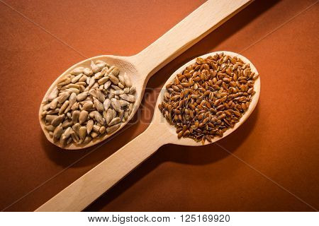 Sunflower seeds and linseed on a wooden spoon on the table