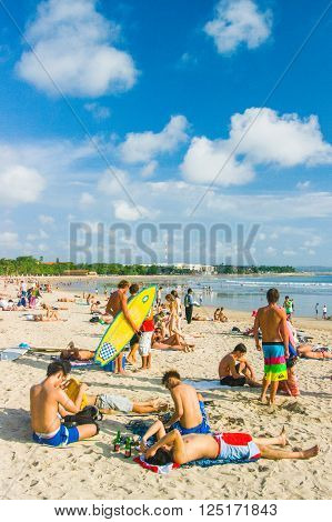 Kuta,Indonesia - JULY 24 : Tourists relax on Kuta Beach on the 24th of july 2009 in BaliIndonesia. Bali is a popular holiday destination especially for young australian and backpackers