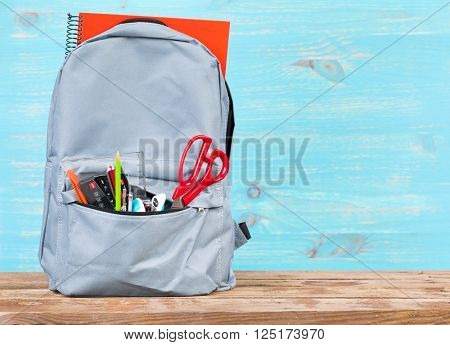 Backpack with school tools on turquoise background