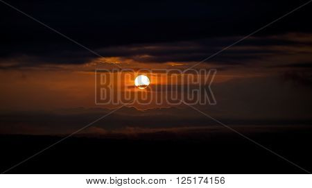 Dramatic sunset between the clouds at Murchison Falls National Park in Uganda, Africa  Intentionally underexposed for dramatic effect
