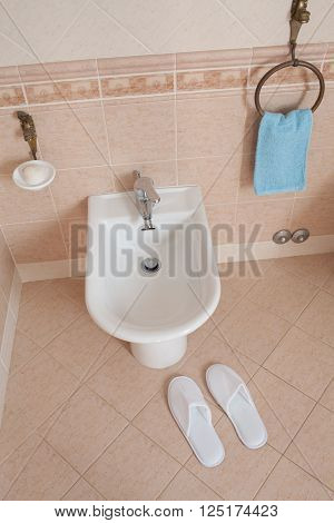 Spa-styled slippers near the bidet inside home bathroom.