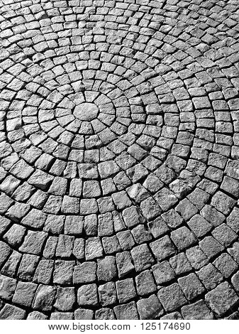Pavement flagstone laid in circular pattern dark grey color.