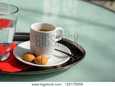 Espresso with a glass of water and cookies on a table