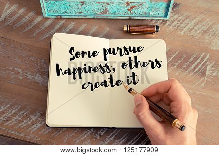 Retro effect and toned image of a woman hand writing on a notebook. Handwritten quote Some pursue happiness, others create it as inspirational concept image