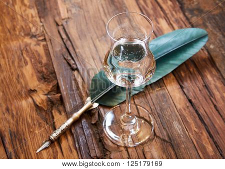 Grappa in a small glas on old wooden table, selective focus