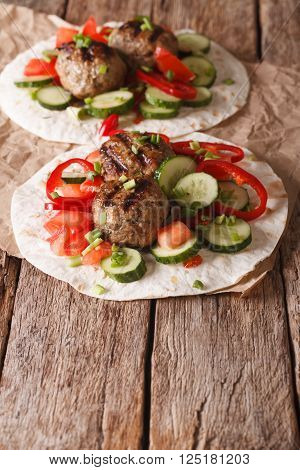 Grilled meat balls with fresh vegetables on a flat bread close up. Vertical