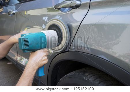 Image of hands worker polish a car body with an auto polisher in the garage