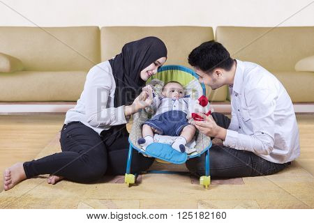 Picture of two happy parents playing with their baby in the stroller at home