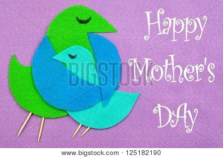 Felt cut out bird shapes in green and blue with toothpick legs and black marker eyes. Mom bird is embracing baby bird. Background is purple color felt with copy space. Happy Mother's Day message