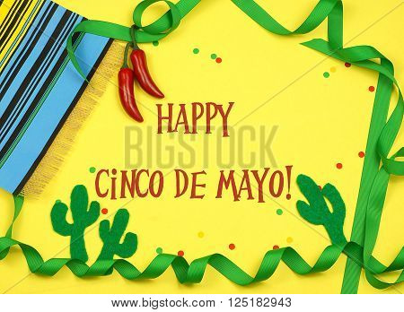 A green ribbon border winds in and out of frame and is decorated with a serape blanket red chilis felt cutout cactus shapes and confetti on a yellow background with Cinco de Mayo message