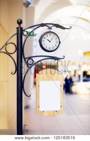 Clock with empty advertisting board inside the building