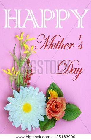 Cheerful silk flowers form a lower left and upper right corner borders on pink background. Copy space available. Good for Mother's Day or birthday wishes