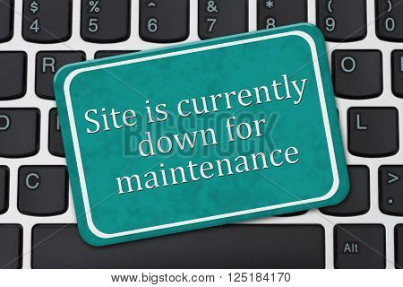 A teal and white sign with the words Site is currently down for maintenance on a computer keyboard
