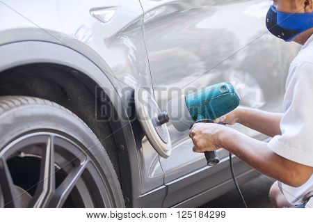 Picture of a male worker polishing a silver car body with an auto polisher machine