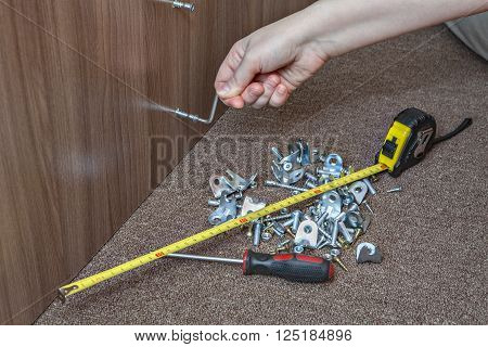 Hand tools for assembling furniture furniture brackets and fasteners closeup hand tighten the screw using the hex key.