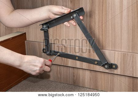 Assembly folding bedroom wooden furniture, lift up bed frame adjustable metal hinge, close-up hand of carpenter screwed screw using red  phillips-head screwdriver.
