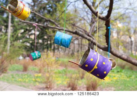 Colored feeding for the wild birds made from tin cans