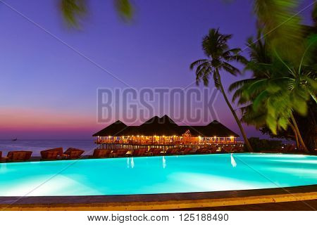 Pool and cafe on tropical Maldives island - nature travel background