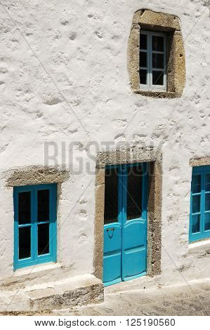 The old entrance to the house in the typical blue color in a stone door frame on the Greek island of Patmos