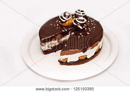 Chocolate cake with nuts and white strew on white plate