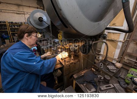 Saint-Petersburg Russia - March 23 2016: Women 50-55 years is working on drilling machines in the metalworking shop