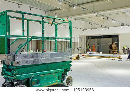 Scissor lift platform is inside of new big hall in building process.