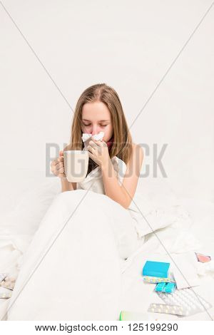Sick Woman With Rheum Sitting In Bed And Holding A Cup Of Tea