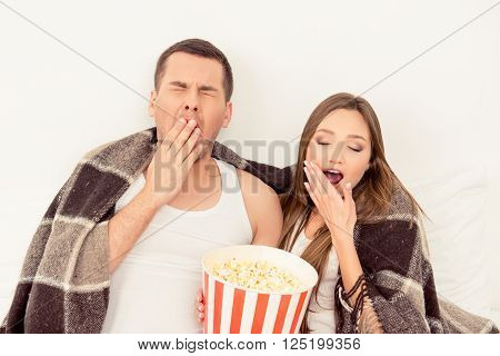 Couple In Love Sitting With Popcorn And Yawning While Watching Film
