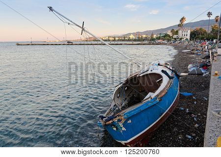 KOS ISLAND, GREECE - OCTOBER 14, 2015: Damaged ship on October 14, 2015 in the harbor of Kos island, Greece. Thousands of Syrian refugees have passed from Turkey to Greek islands during the summer of 2015.