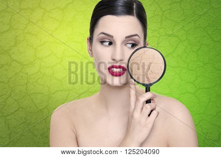 Beautiful girl with dry skin problem and magnifier skin pores on green background
