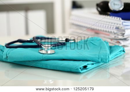 Medical Stethoscope Lying On Green Doctor Uniform Closeup