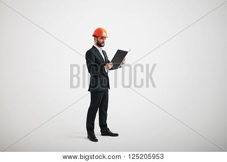 Serious man in a formal wear and hard hat looking at black folder in his arms