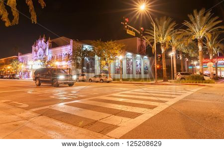 Pasadena,California, USA - October 3, 2015: Pedestrian crossing from car park on West 4th St building to movies and California Theatre of the Performing Arts night scene showing of the retro era neon lighting in San Bernardino California USA