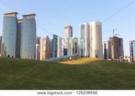 DOHA, QATAR - FEBRUARY 9, 2016: Residents relax on the newly finished artificial grass-covered hills of Hotel Park, in the shadow of the commercial towers of the Dafna district of the Qatari capital