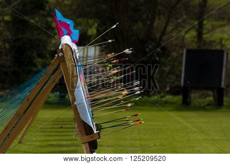 Arrows embedded in row of archery targets. Arrows sticking out from multiple targets after shooting in a competition with flags on a windy day