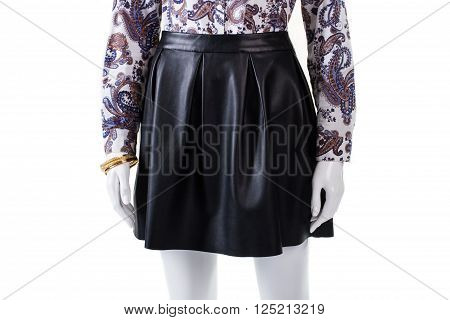 Dark leather skirt on mannequin. Woman's gold bracelet and skirt. Black skirt with folds. High-quality garment and jewelry.