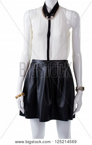 Mannequin wearing thin sleeveless blouse. Dark skirt and sleeveless blouse. Thin blouse with precious accessories. Stylish look for modern girls.