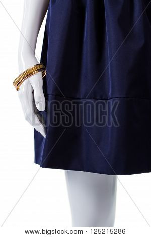 Mannequin wearing skirt and bracelet. Bracelet and skirt with folds. Lady's new gold bracelet. Expensive piece of jewelry.