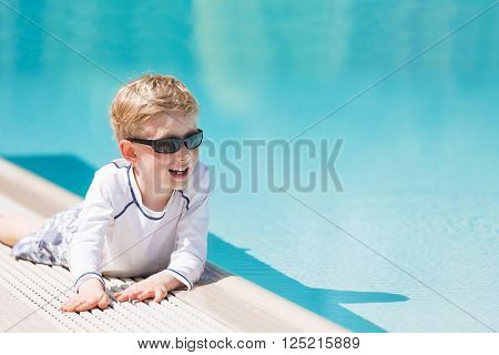 smiling excited boy in sunglasses and rashguard enjoying warm weather in swimming pool vacation and sun protection concept
