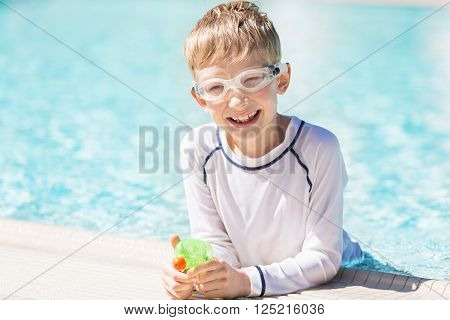 smiling excited boy with beach toy in goggles and rashguard enjoying warm weather in swimming pool vacation and sun protection concept