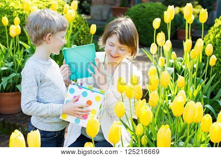 happy smiling mother and her loving son giving a present and spending time together in the beautiful blooming park at spring time, mother's day concept