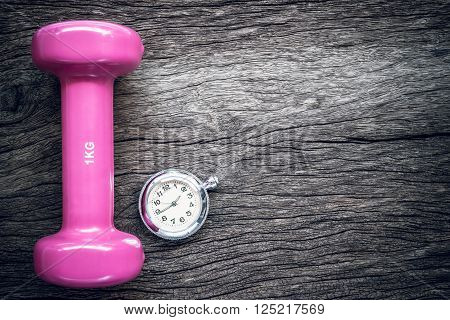 Time for exercising pocket watch and dumbbell on wooden background.
