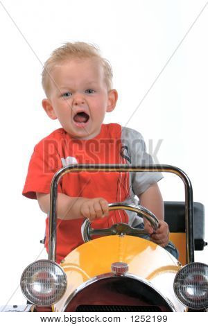 Blond Boy Driving A Toy Car