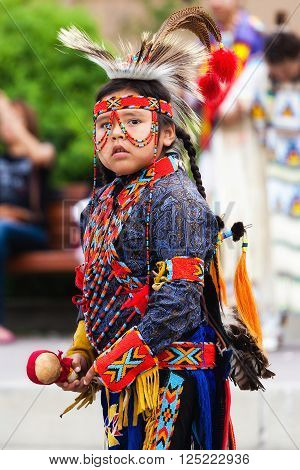 BANFF, CANADA - JUL 3: A young native Blackfoot Indian dancer gets ready for his performance during the Banff Summer Arts festival July 3 2014. The Banff Summer Arts Festival is the longest running arts festival in Canada held every summer since 1933.