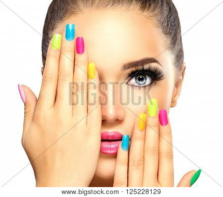 Beauty Girl Face with Colorful Nail polish. Colourful Studio Shot of young Woman. Vivid Colors. Colourful Manicure and fashion Makeup. Rainbow Colors. Beautiful lady touching face. Isolated on white