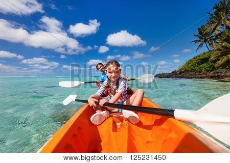 Family father and daughter enjoying paddling in colorful red kayak at tropical ocean water during summer vacation