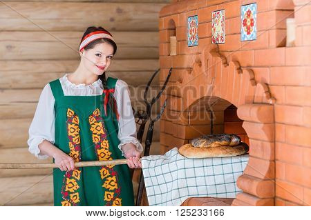 Woman Bakes Bread In A Russian Stove
